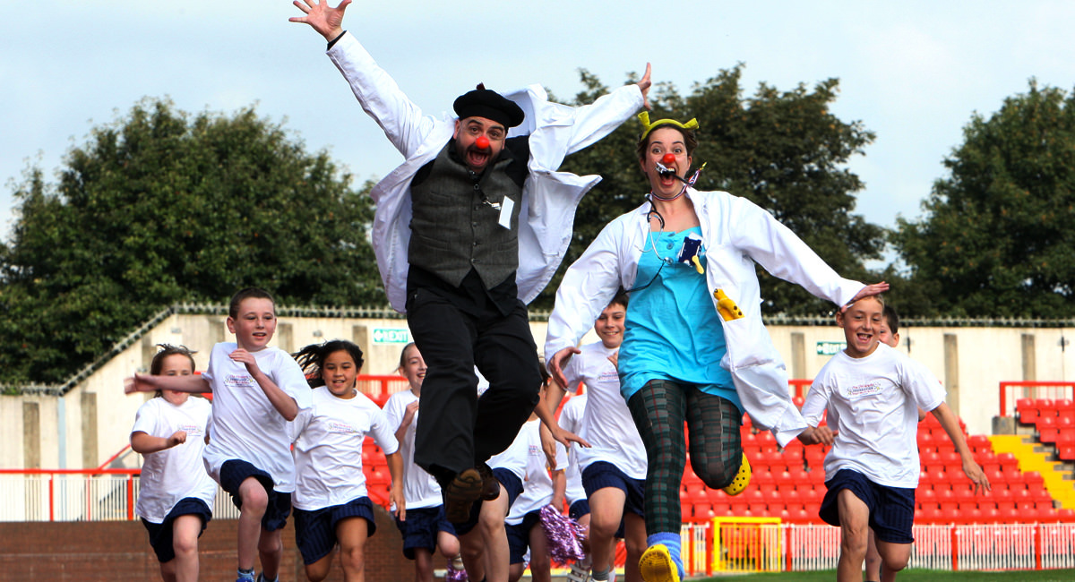 Doctors with red noses and children on a running track
